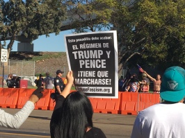 "A woman holds a sign saying, ""El Régimen de Trump y Pence ¡Tiene Que Marcharse! (The regime of Trump and Pence has to go!"". Photo Credit: Roberto A. Camacho"