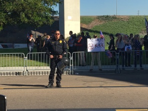 "SDPD officer next to a individual holding a sign saying, ""We hate KKK"". Photo Credit: Robert A. Camacho"