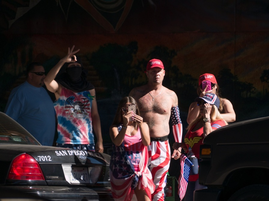 John Turano pictured here in Chicano Park next to a masked individual throwing up a mock white power hand gesture.