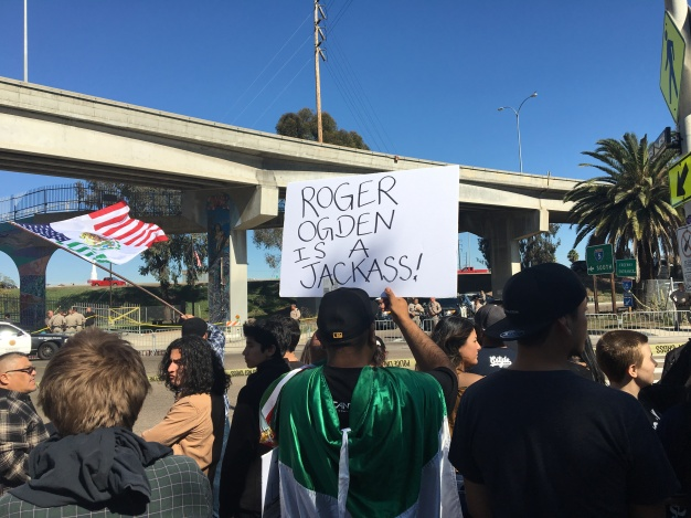 "Man holds sign saying, ""Roger Ogden Is A Jackass!"". Photo Credit: Roberto A. Camacho"